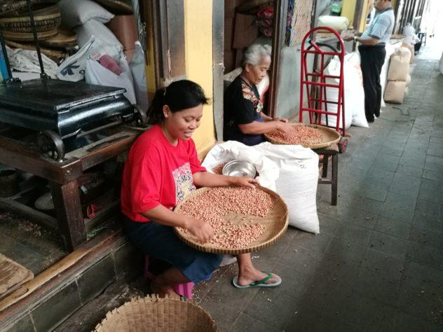 Erdnüsse kann man hier fertig geschält kaufen - die Frauen hier sortieren noch Schalen aus